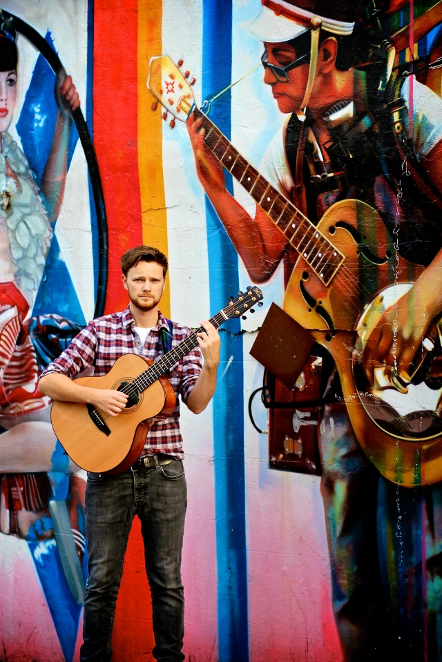 Duelling Guitars: Elliott Morris in good company by Brazilian artist Eduardo Kobra's street mural on the back wall of The Roundhouse, Chalk Farm (Photo copyright: Vanessa Haines Photography)